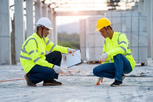 Gresham workers checking cement foundation floor